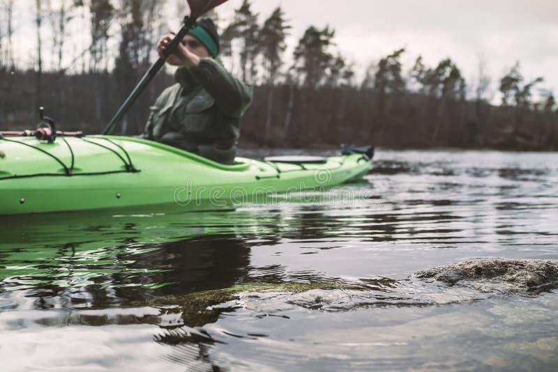 皮船的一年轻人在一个湖浮动,沿岩石岸,反对树被弄脏的背景  r 免版税库存图片