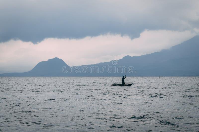 皮船的人在山前面的湖 免版税库存照片
