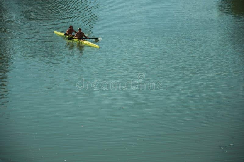 皮船的人用浆划在瓜迪亚纳河的在梅里达 免版税图库摄影