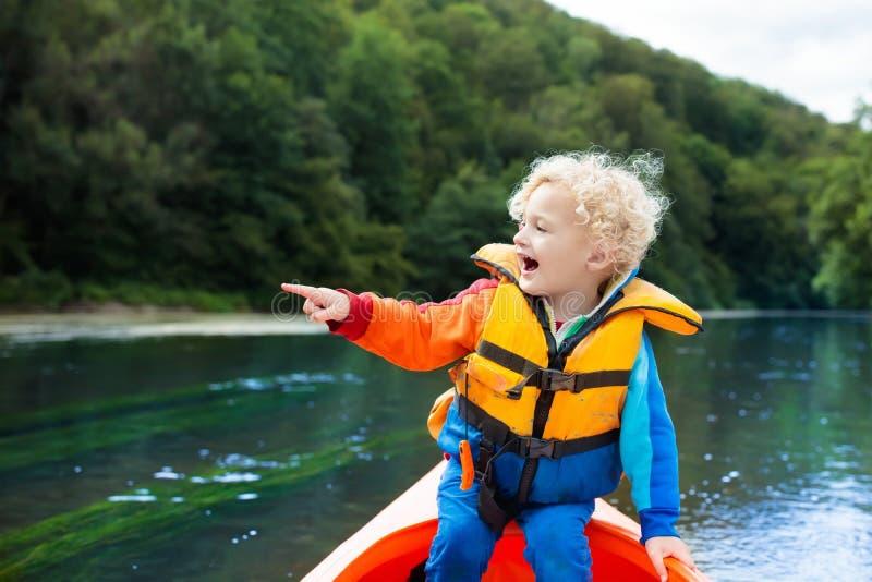 皮船的孩子 在独木舟的孩子 夏天野营 免版税库存图片