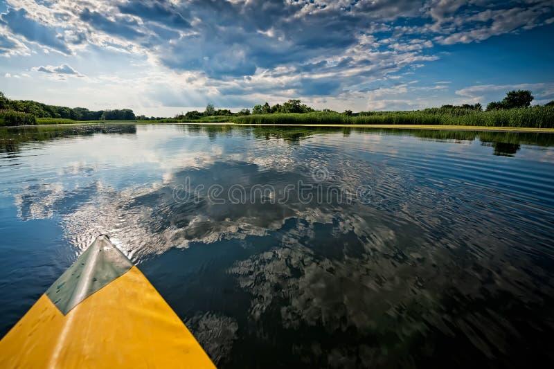 从皮船的看法在河,有岸的一个森林的和蓝色 库存图片