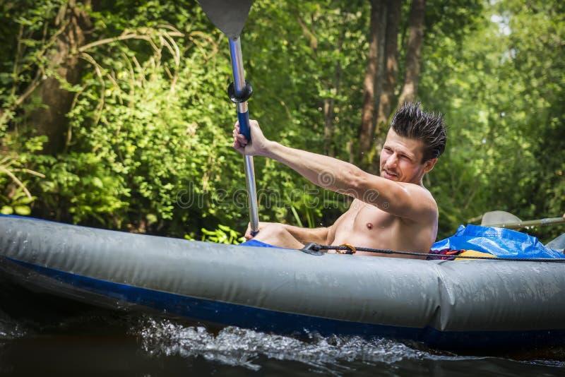 皮船的运动的年轻人有桨的 划皮船的 免版税库存照片