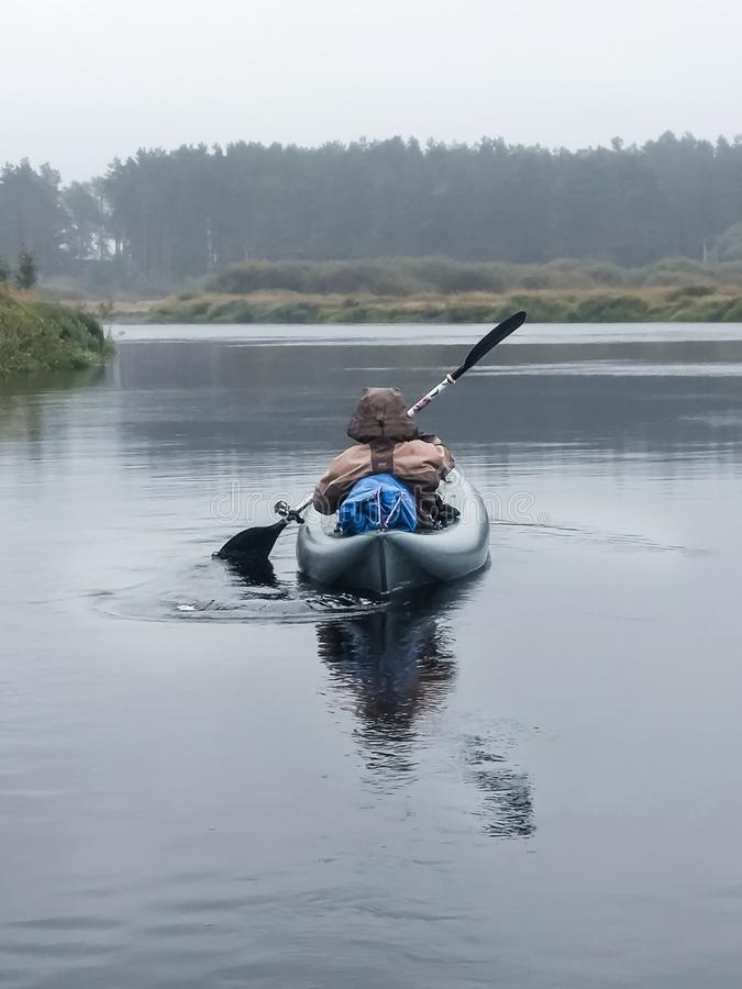 皮艇人桨皮船背面图在河 免版税库存图片