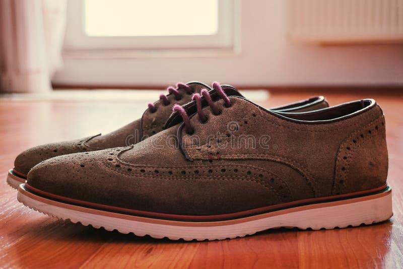 皮革人的有色的鞋带的方鞋子在与后面光的地板上 库存图片