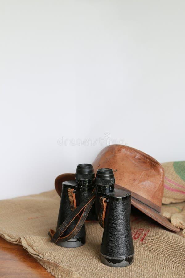 皮革帽子、双筒望远镜和粗麻布 免版税库存照片
