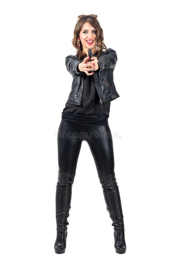 黑皮革指向的枪的愉快的微笑的可爱的妇女在照相机 库存图片