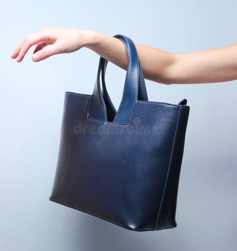 皮革提包在女性手上垂悬 免版税图库摄影