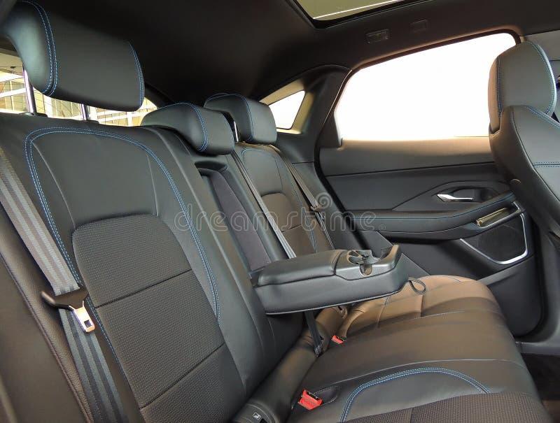 皮革整理了有杯座的折叠的扶手在车里面的后座 库存照片