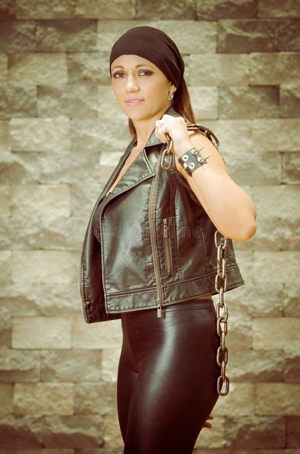 皮革的一名年轻和美丽的拉提纳帮会妇女 免版税库存照片