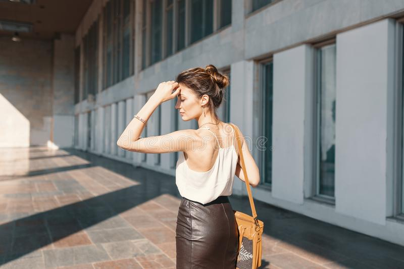 皮革裙子和丝绸女衬衫的被提炼的年轻女人认为如何的解决情况 免版税图库摄影
