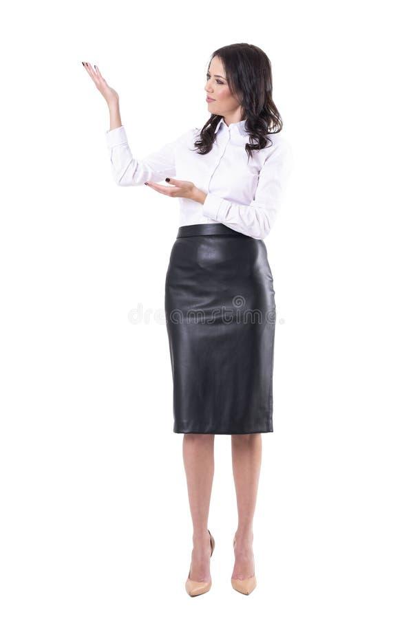 皮革黑卖产品的裙子和白色衬衫的愉快的正面俏丽的女商人 免版税库存图片