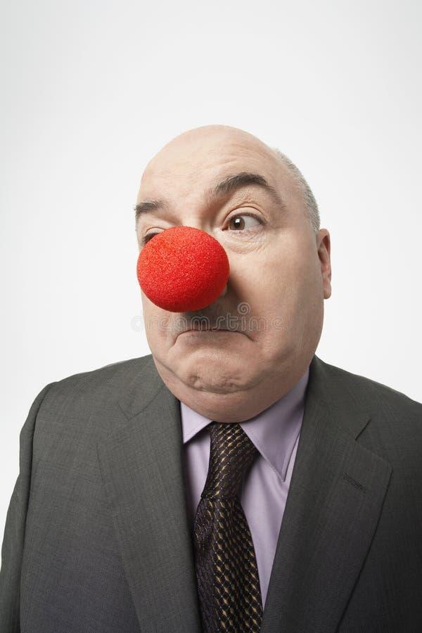 皱眉商人佩带的小丑的鼻子 免版税库存照片