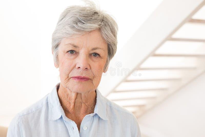 皱眉在照相机的退休的妇女 库存照片