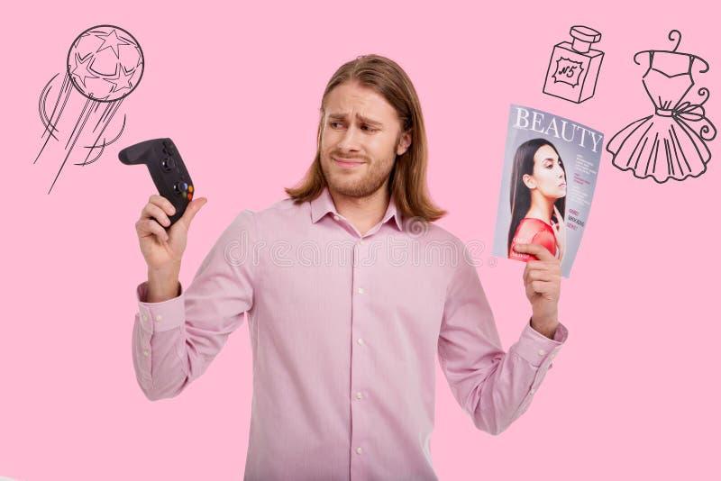 皱眉担心的人,当选择在人比赛和妇女杂志之间时 库存照片