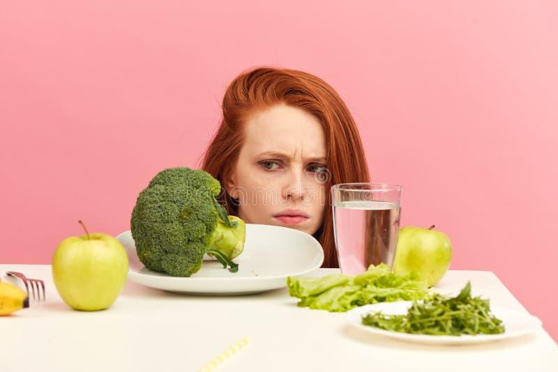 皱眉的妇女烦恶在桌上的菜与憎恶的鬼脸 免版税库存图片