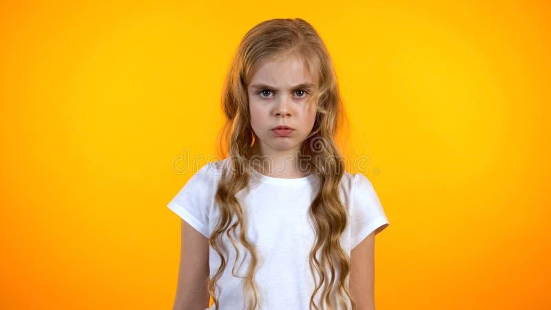 皱眉让烦恼的严肃的女孩看对照相机和,隔绝在橙色背景 库存照片
