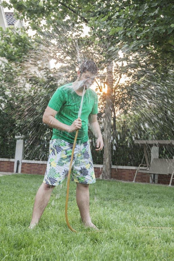 盆射的年轻人与在面孔的一条水管,户外在庭院里 库存图片