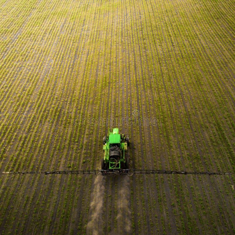 盆射领域的拖拉机与化学制品在春天 免版税库存图片