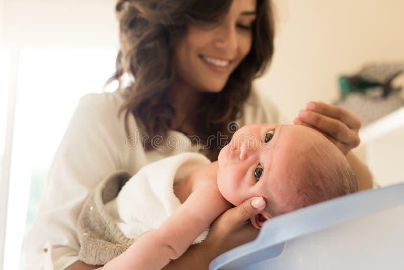 浴盆的母亲洗涤的婴孩 免版税图库摄影