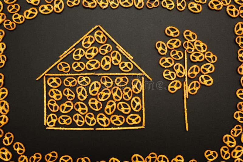 盐味的椒盐脆饼和微型棍子背景纹理以一个房子和一棵树的形式在黑背景 库存照片