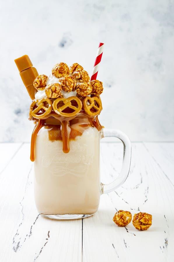 盐味的焦糖纵容极端奶昔用brezel奶蛋烘饼、玉米花和打好的奶油 疯狂的freakshake趋向 免版税库存图片