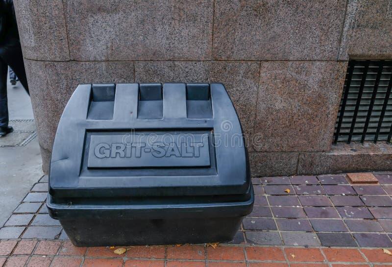 盐和沙粒的大黑塑胶容器 为坏和冰冷的天气准备 免版税库存照片
