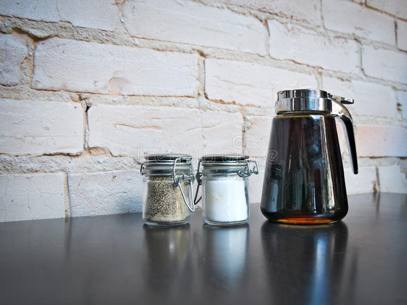 盐和胡椒罐和糖浆分配器在咖啡馆桌上在砖墙旁边 免版税库存照片