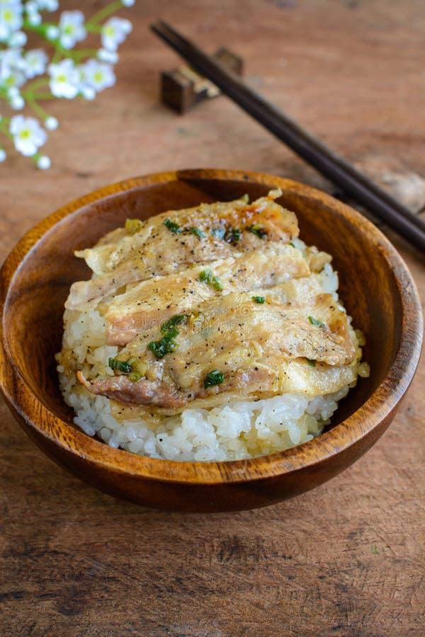 盐和黑胡椒烤了猪肉用在木的日本米 免版税图库摄影