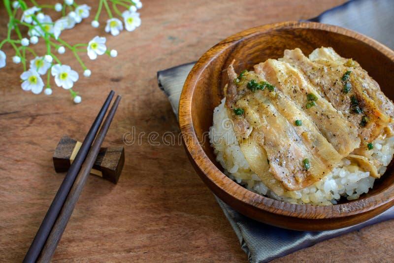 盐和黑胡椒烤了猪肉用在木的日本米 免版税库存照片