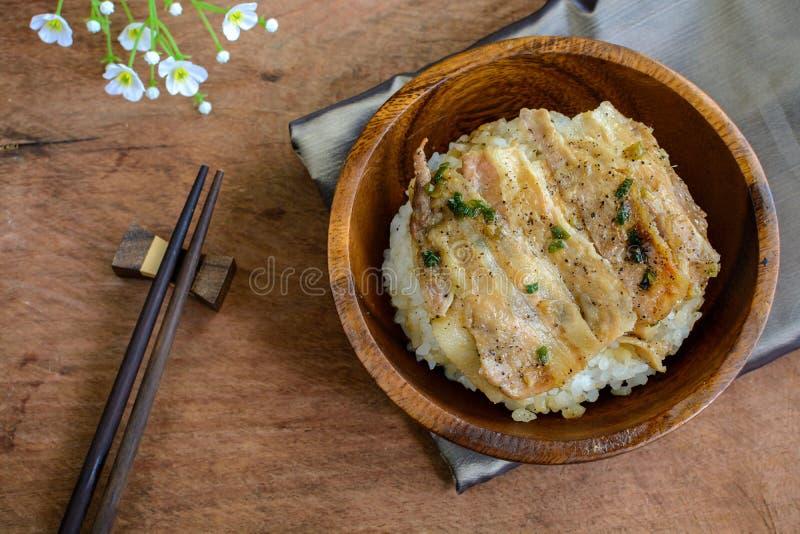 盐和黑胡椒烤了猪肉用在木的日本米 免版税库存图片