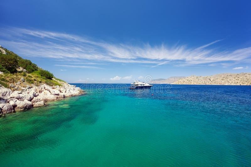 盐水湖在九头蛇海岛,希腊 透明的绿松石水 有停泊绳索的豪华游艇反对岩石 免版税库存照片