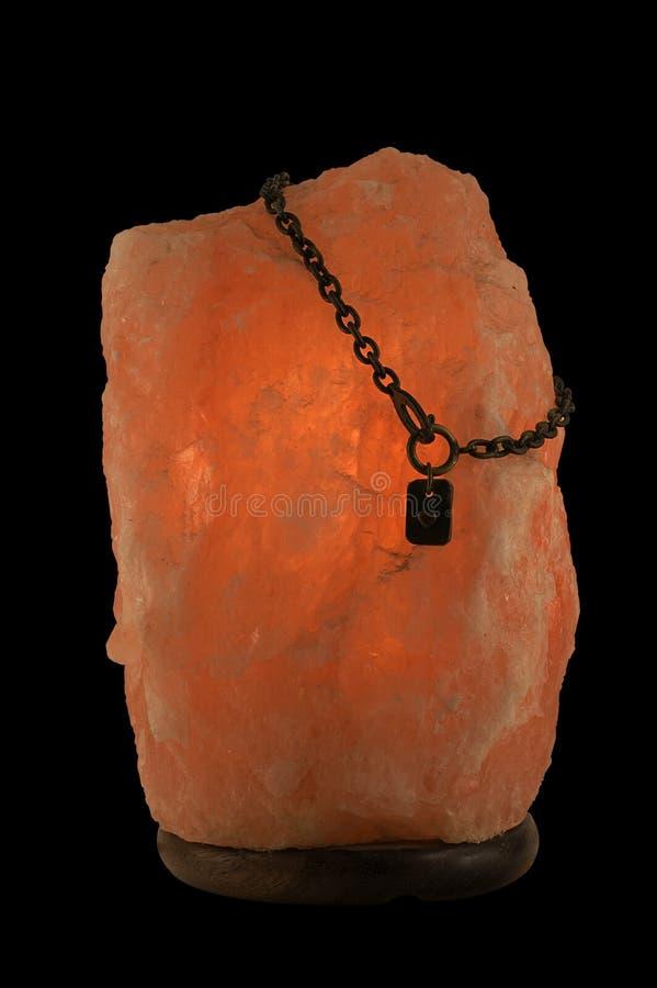盐溶有被隔绝的链子和心脏的灯在黑背景 免版税库存照片
