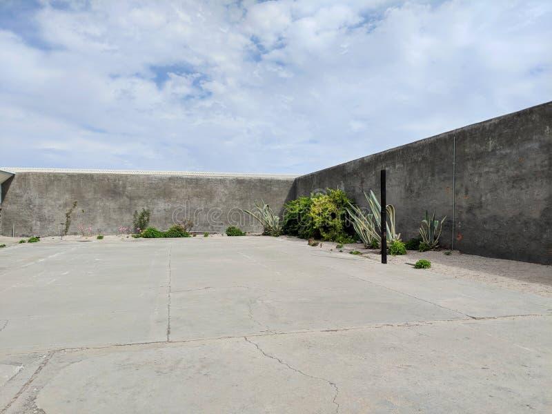 监狱院子、云彩天空和墙壁 库存图片