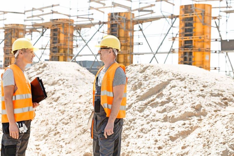 监督员侧视图谈论在建造场所 免版税库存照片
