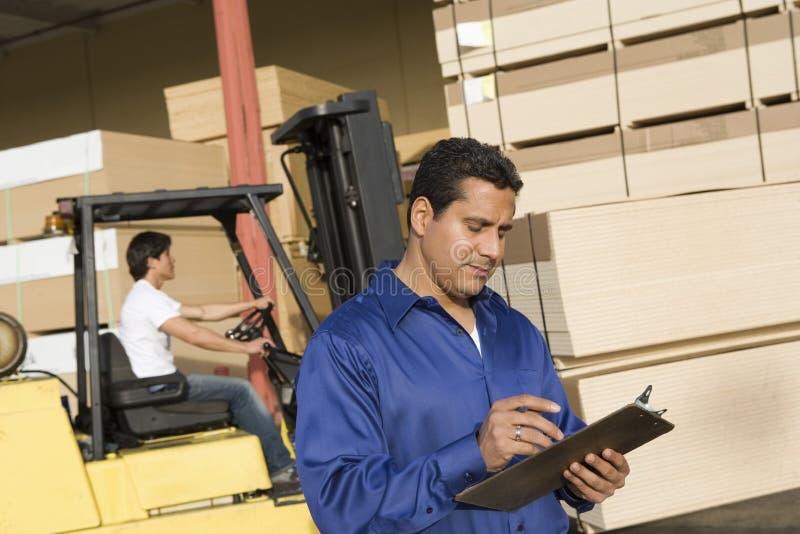 监督员和叉架起货车司机 免版税库存图片