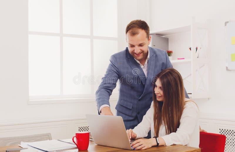 监督他的在便携式计算机上的商人女性助理的工作 免版税库存照片