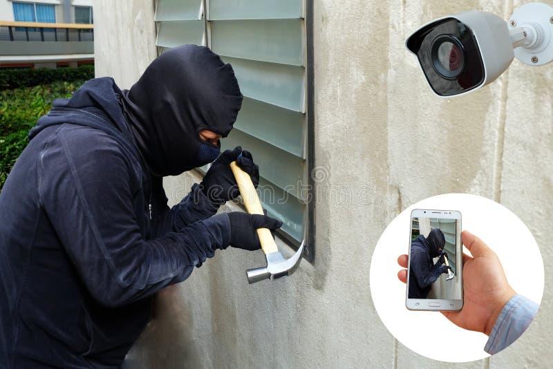 监视器捕获和纪录捉住了有拿着手机的锤子和手的被掩没的窃贼查出在应用 库存图片