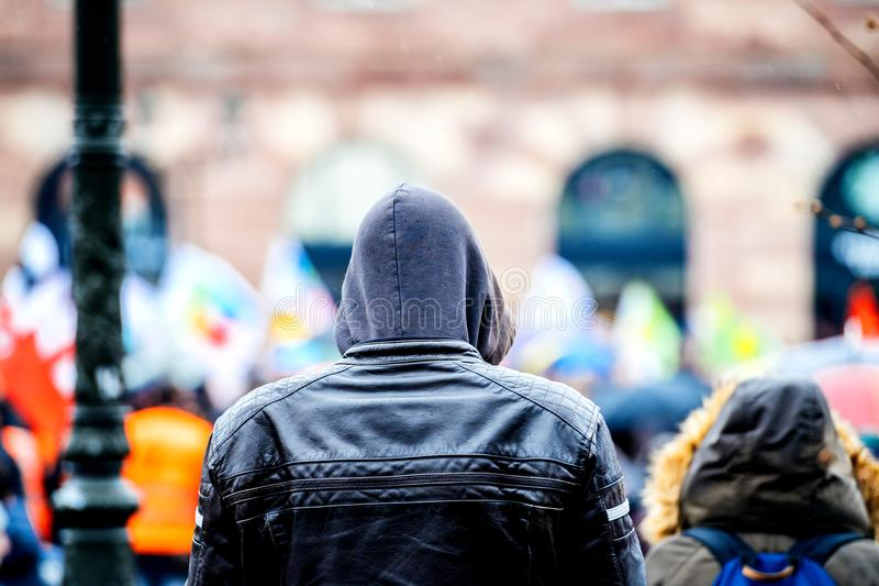 监视年轻人佩带的有冠乌鸦外套抗议背面图  免版税图库摄影
