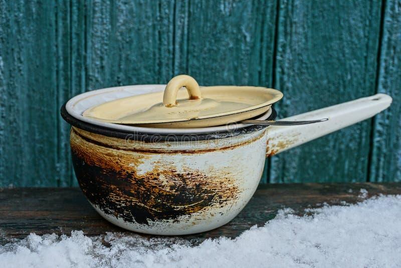 盒盖盖的老被烧的平底深锅在白雪的一张木桌上站立对在街道的绿色墙壁 库存照片