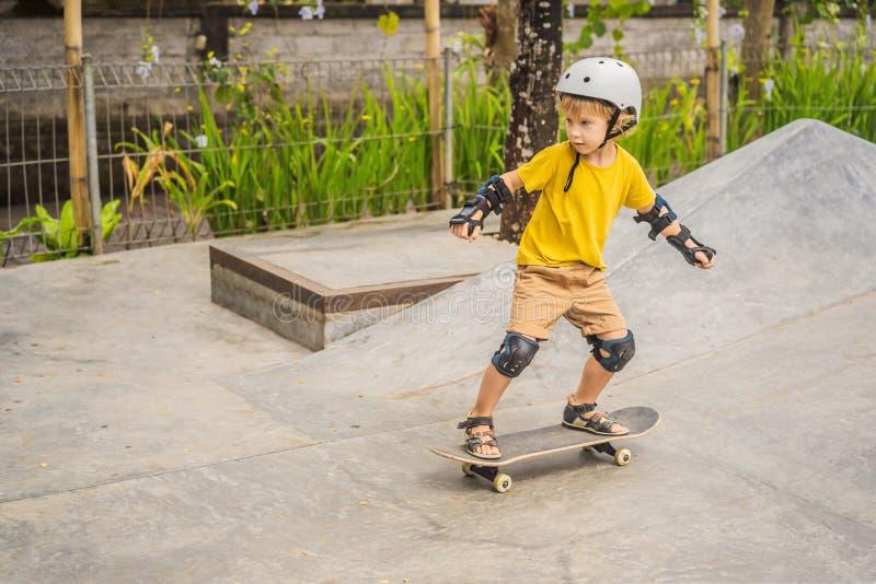 盔甲和护膝的运动男孩学会踩滑板与在冰鞋公园 儿童教育,体育 图库摄影