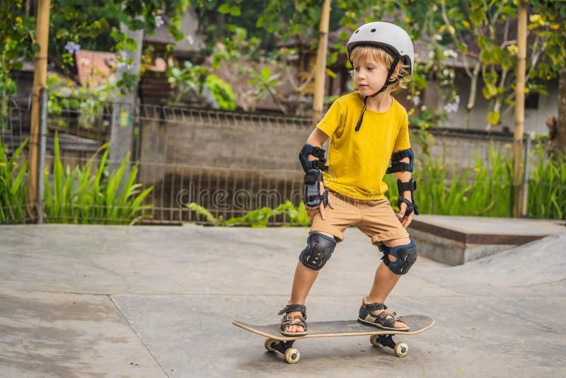 盔甲和护膝的运动男孩学会踩滑板与在冰鞋公园 儿童教育,体育 库存图片