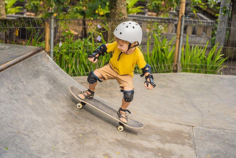 盔甲和护膝的运动男孩学会踩滑板与在冰鞋公园 儿童教育,体育 库存照片