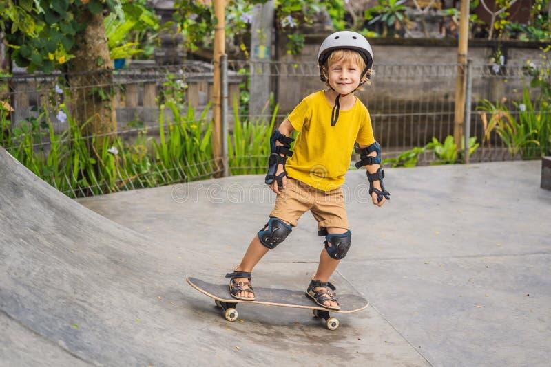 盔甲和护膝的运动男孩学会踩滑板与在冰鞋公园 儿童教育,体育 免版税库存照片