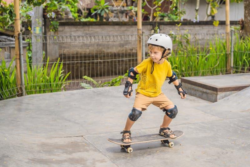 盔甲和护膝的运动男孩学会踩滑板与在冰鞋公园 儿童教育,体育 免版税库存图片