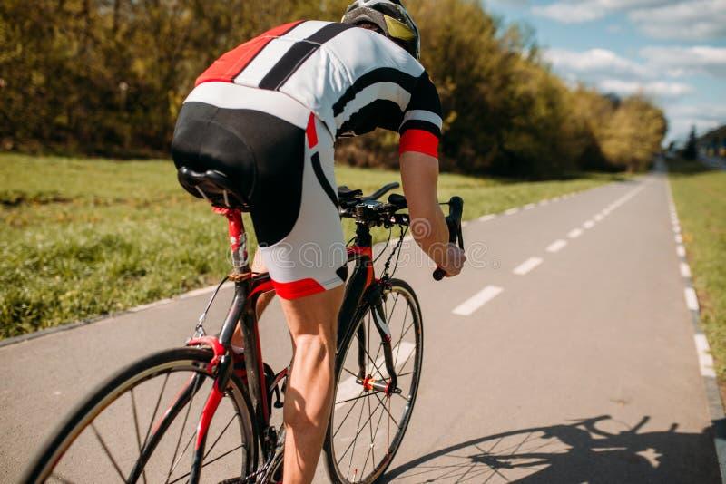 盔甲和运动服的骑自行车者在自行车乘坐 免版税库存图片