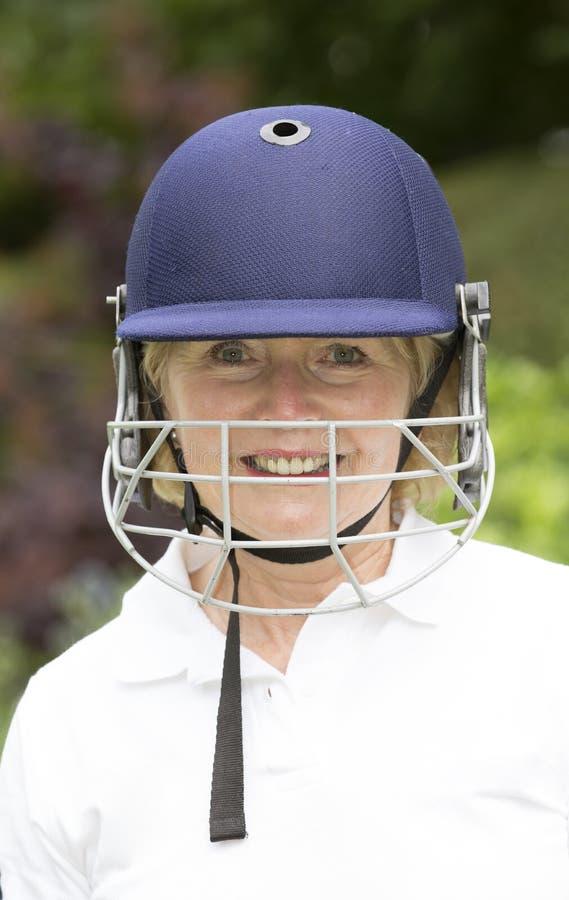 头戴盔甲的一名年长女性玩板球者的画象 免版税库存图片