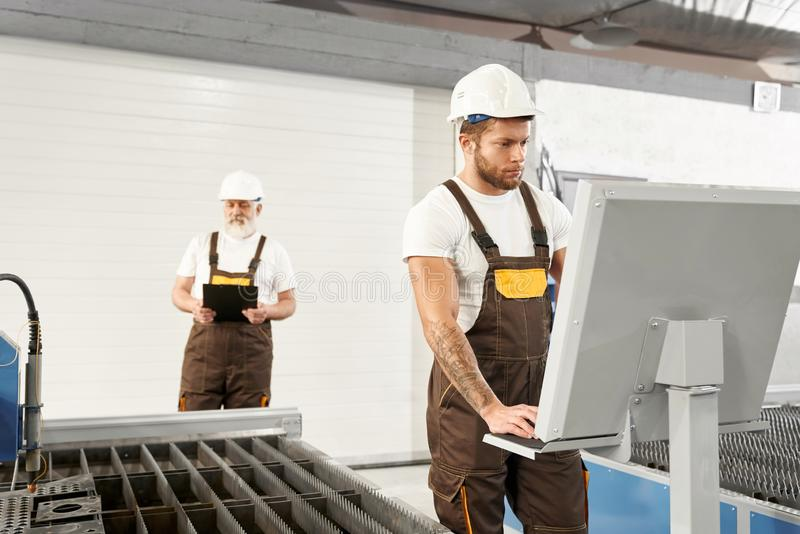 盔甲的两位在工作的过程中工程师和制服 免版税库存照片