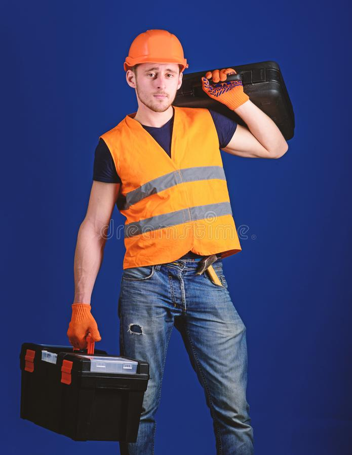 盔甲的人,安全帽拿着工具箱和手提箱有工具的,蓝色背景 被装备的安装工概念 工作者 免版税库存照片