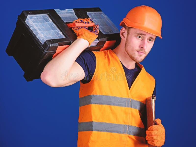 盔甲的人,安全帽拿着工具箱和文件夹与文件,蓝色背景 修理公司概念 安装工 免版税库存图片