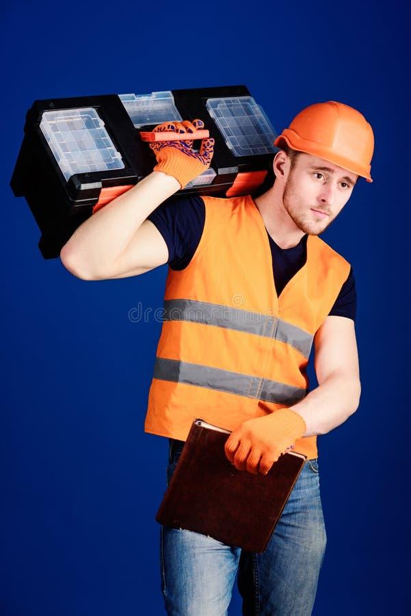 盔甲的人,安全帽拿着工具箱和文件夹与文件,蓝色背景 修理公司概念 工作者 库存照片